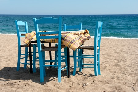 Greek beach with traditional blue table and chairs Stock Photo