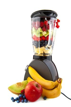 licuadora: Licuadora y fruta fresca que aseg� aislados sobre blanco