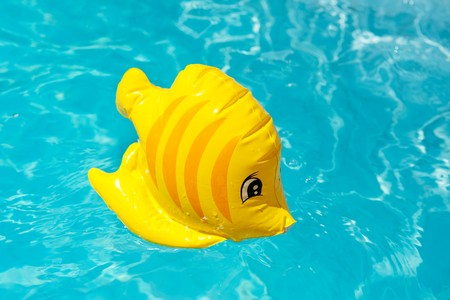 floatable: Floatable fish toy in the clear swimming pool Stock Photo
