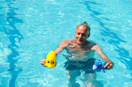 Retired man is playing in the swimming pool  photo