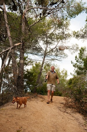 Elderly man is walking the dog in the forest photo