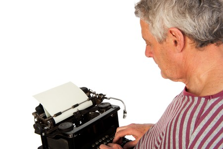 Elderly man is writing with an old antique black typewriter photo