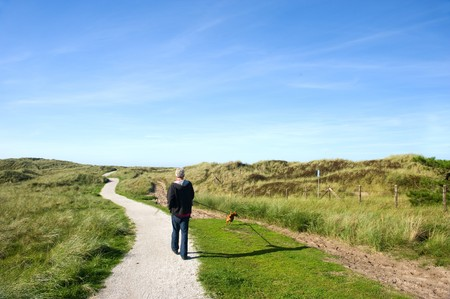 Walking the dog in coast landscape with sand dunes at Ameland Stock Photo - 8056299
