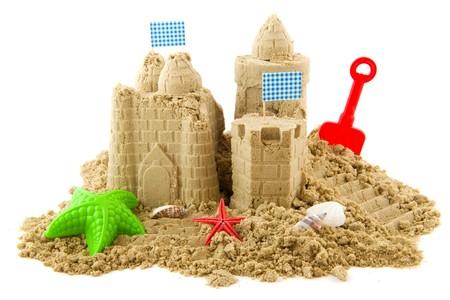 castillos: Castillo de arena en la playa en vacaciones aislada en blanco  Foto de archivo