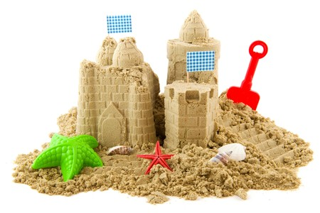 Sandcastle at the beach on vacation isolated over white