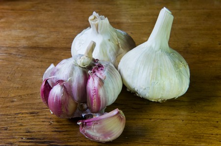 Fresh red garlic on wooden table in kitchen photo