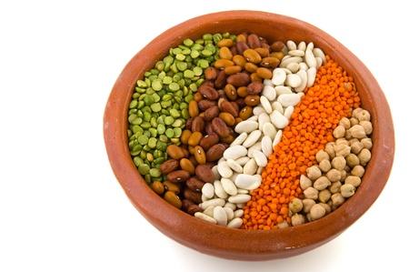 leguminosas: Varias de las legumbres en iver de vajilla marr�n aislado de barro blanco Foto de archivo