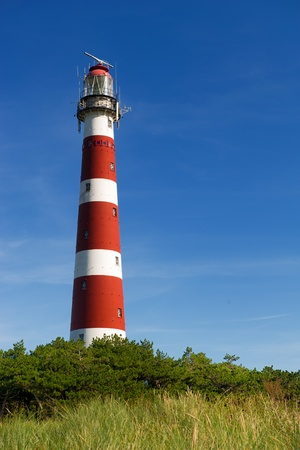 Classic lighthouse in red and white in front of blue sky
