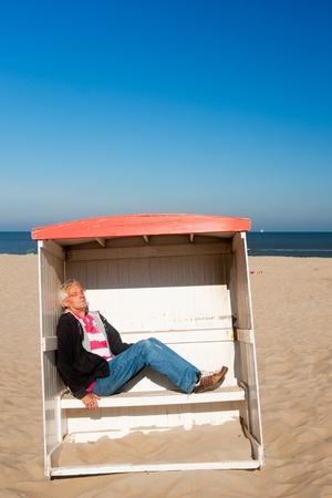 Man is sleeping in a classic beach chair  photo