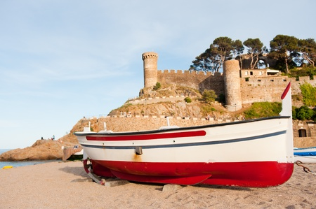 Fishing boat in front of the castle in Tossa de Mar at the Spanish coast photo