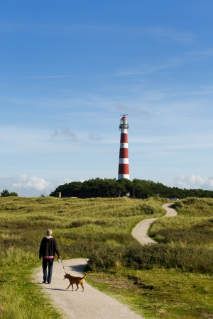 Man is walking his dog near the lighthouse Stock Photo - 8315801