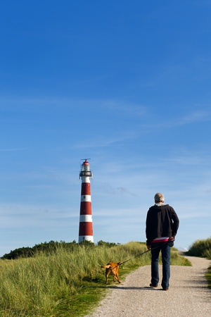 Man is walking his dog near the lighthouse Stock Photo - 8315785