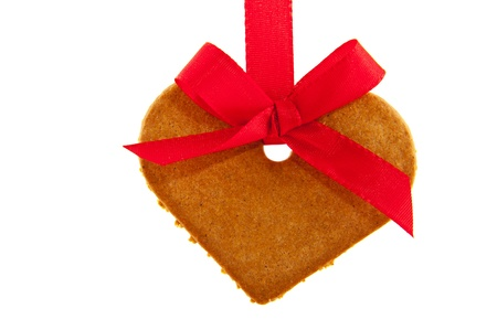 Ginger bread heart hanging at red ribbon isolated over white photo