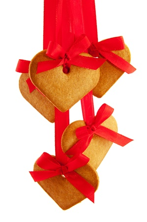 Ginger bread hearts hanging at red ribbon isolated over white photo