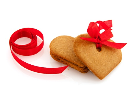 Ginger bread hearts with red ribbon isolated over white photo