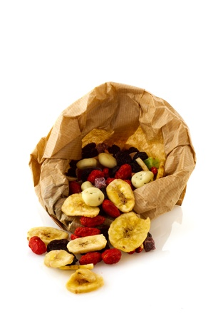 Open paper bag with dried fruit isolated over white background photo