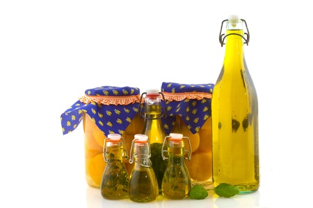 Preservate peaches in glass pots and bottles olive oil with herbs photo