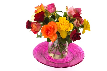 Glass vase with colorful bouquet of roses on pink plate photo