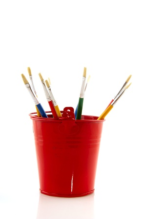Paint brushes in red little bucket isolated over white background photo