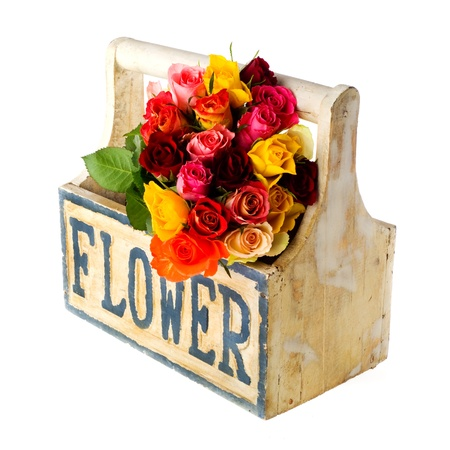 Wooden crate with bouquet of colorful roses isolated over white photo