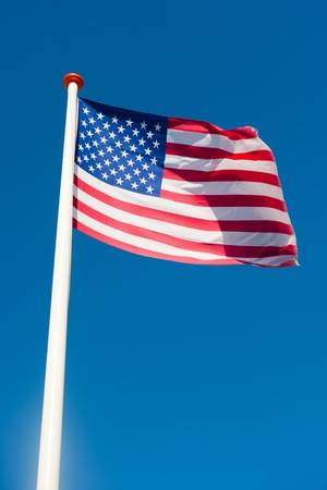 U.S. American flag in front of a blue sky