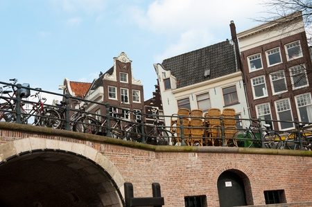 Canal houses with bikes and terrace seats at the bridge photo