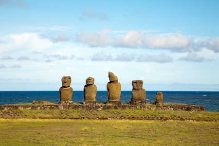 Row with old statues at Easter island in front of the sea photo