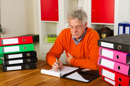 Elderly man is sitting with many paper folders and writing a letter photo