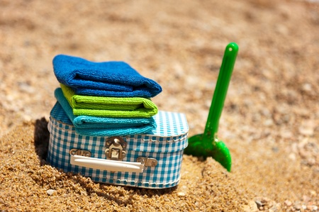 Suitcase and toys at the summer beach on vacation photo