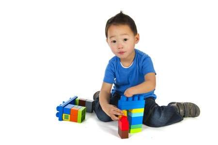 little Chinese boy with one smaller hand is playing with colorful blocs