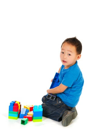 special needs:  Chinese boy with light handicap is playing with blocs