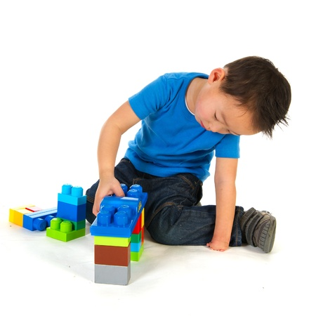 special needs: Chinese boy with one smaller hand is playing with colorful blocs Stock Photo