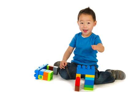 special needs: Happy smiling Chinese boy with little handycap playing with colorful blocs