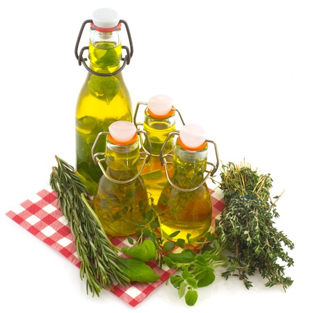 flavored: Olive oil with verious kinds of fresh herbs isolated over white Stock Photo
