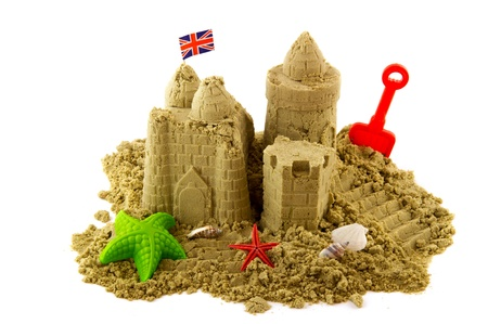 Sandcastle at the beach on vacation isolated over white photo