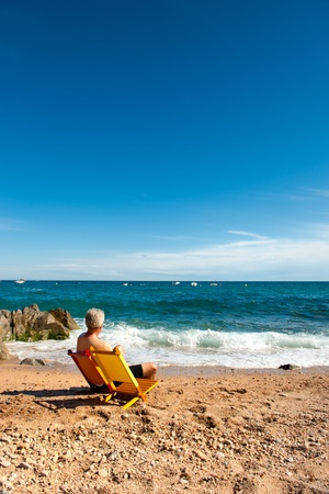 Elderly man is relaxing at the tranquil beach Stock Photo - 8792908