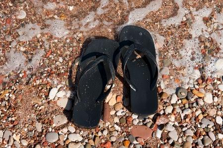 Black flip flops at the summer beach photo