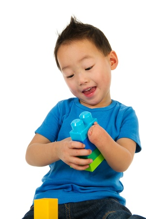 special needs: Happy Chinese boy with light handicap is playing with colorful blocs Stock Photo