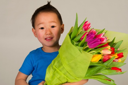 asian tulips: Little cute Asian boy with bouquet colorful tulips