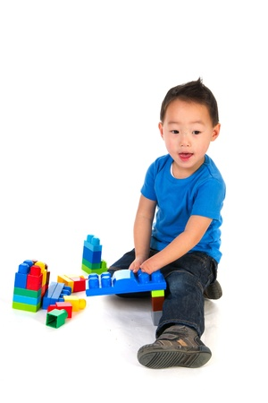 special needs: Light physically handicapped Chinese boy playing with colorful blocs Stock Photo