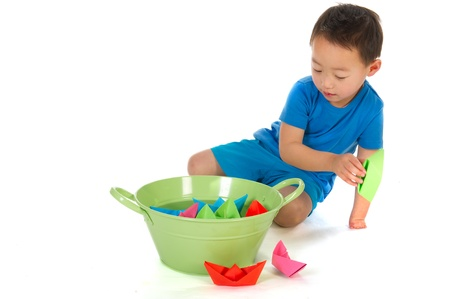 special needs: Little Chinese boy with handicap on hand is playing with paper boats isolated over white Stock Photo
