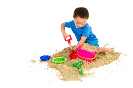 sandbox: Chinese boy playing at the beach isolated over white Stock Photo