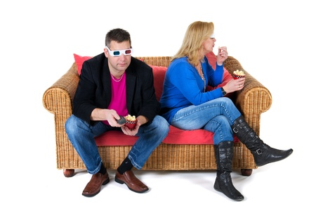 Couple is sitting at the coach and looking 3D televison photo
