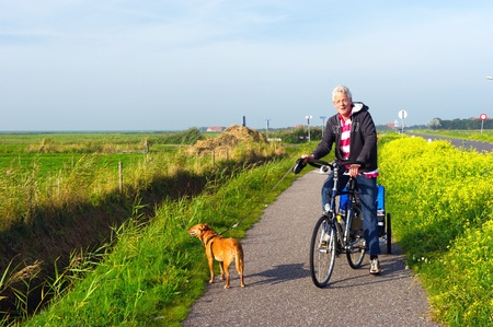 coleseed: Man with his dog at the bike in Dutch landscape
