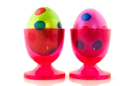 Colorful easter eggs in pink cups isolated over white photo