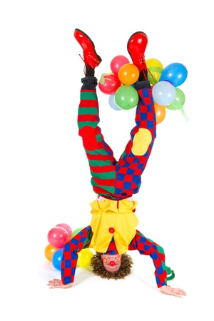 Funny clown with balloons in headstand on white background
