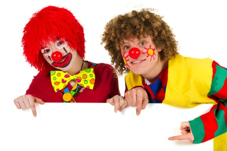 Two funny clowns are pointing to an empty white board for text photo