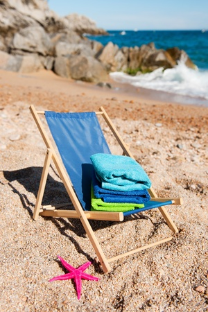 Empty beach chair with stack of towels near the sea photo