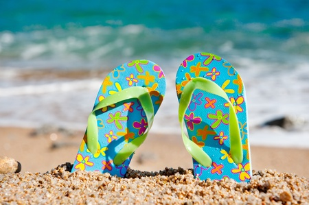 flip flops: Flip flop sandals at the beach near the water line