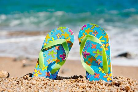sandalia: Voltear sandalias de fracaso en la playa cerca de la l�nea de agua Foto de archivo